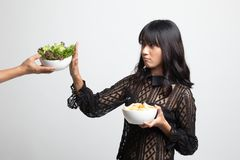 Young Asian woman with potato chips say no to salad. On white background stock image