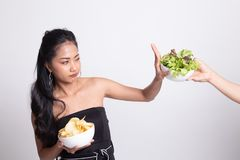 Young Asian woman with potato chips say no to salad. On white background stock photo