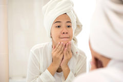 Young asian woman pressing her face, trying remove acne Stock Photos
