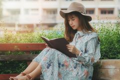 Young asian woman reading a book on the bench Stock Image