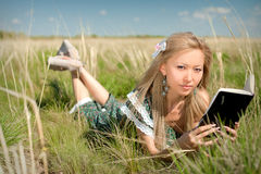 Young asian woman reading book on a nature Royalty Free Stock Photography