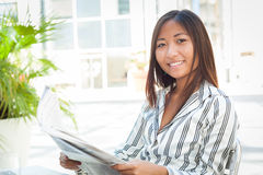 Young asian woman reading newspaper Royalty Free Stock Photos