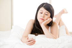 Young asian woman reading use smart phone on bed Royalty Free Stock Photo