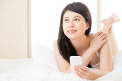 Young asian woman reading use smart phone on bed Royalty Free Stock Images