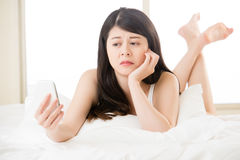 Young asian woman reading use smart phone on bed Royalty Free Stock Image