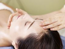 Young asian woman receiving face massage in spa salon. Close-up of beautiful young asian woman receiving face massage in spa salon, eyes closed Stock Photo