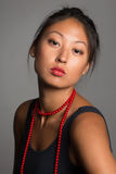 Young Asian woman with red beads. Royalty Free Stock Image