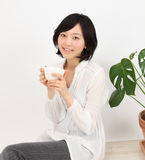 Young asian woman relax with a cup Stock Photo