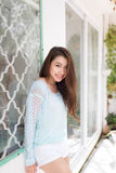 Young asian woman relaxing on a balcony  enjoying fresh air. Royalty Free Stock Photography