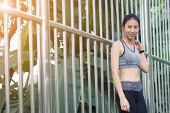 Young asian woman relaxing after jogging exercise stand against steel in park to freshen her body and enjoy warm light in morning. Young woman relax from Stock Image