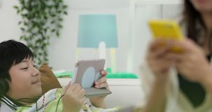 Young asian Woman relaxing and listening to music with young boy. Playing on tablet computer in the living room stock video