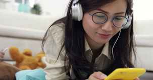 Young asian Woman relaxing and listening to music with young boy. Playing on tablet computer in the living room stock footage