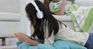 Young asian Woman relaxing and listening to music with young boy. Playing on tablet computer in the living room stock video footage