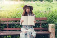 Young asian woman in retro dress sitting on the bench in park. She holding empty blank notebook, showing you something in notebook royalty free stock images