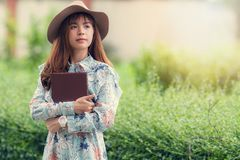 Young asian woman in retro style with a book strolling in park stock photography