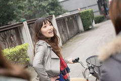 Young Asian woman riding bicycle with friends Royalty Free Stock Photography
