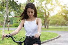 Young Asian woman in riding a bicycle in a park. Active people w Stock Photography