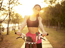 Young asian woman riding bike outdoors at sunset Royalty Free Stock Photos