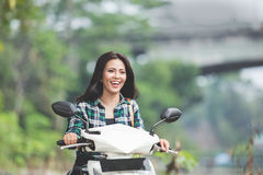 Young asian woman riding a motorcycle in a park Royalty Free Stock Image