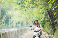 Young asian woman riding a motorcycle in a park Stock Photography