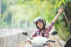 Young asian woman riding a motorcycle in a park Royalty Free Stock Photos