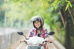 Young asian woman riding a motorcycle in a park Stock Photo
