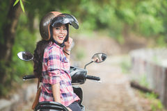 Young asian woman riding a motorcycle in a park. A portrait of a young asian woman riding a motorcycle in a park Stock Image