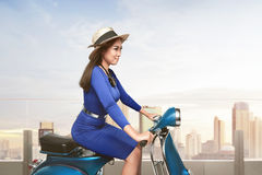 Young asian woman riding scooter Stock Photo