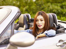 Young asian woman riding in a sports car Stock Photos