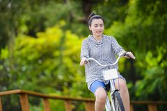 Young asian woman riding a vintage bicycle in a park.  stock photos