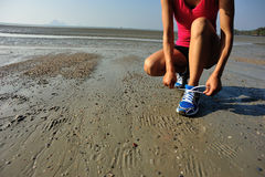 Young asian woman runner tying shoelace Stock Image