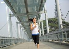 Young asian woman running at modern city footbridg Royalty Free Stock Photos