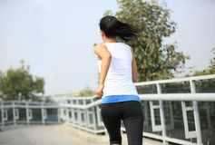 Young asian woman running at modern city footbridg Royalty Free Stock Images