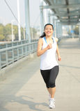 Young asian woman running at modern city footbridg Royalty Free Stock Photography