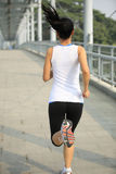 Young asian woman running at modern city footbridg Royalty Free Stock Photo