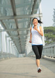 Young asian woman running at modern city footbridg Stock Photos