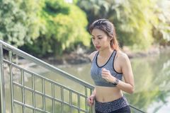 Young asian woman running on sidewalk in morning. Health conscious concept with copy space. Royalty Free Stock Photo