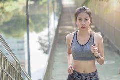 Young asian woman running on sidewalk in morning. Health conscious concept with copy space. Royalty Free Stock Photos
