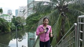 Young asian woman running on sidewalk in morning. Young sport asian woman running upstairs on city stairs.