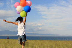 Young asian woman running on sunset grassland with colored balloons Royalty Free Stock Images