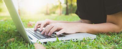 Young asian woman`s legs on the green grass with open laptop. Girl`s hands on keyboard. Distance learning concept. royalty free stock images