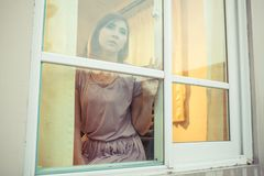 Young asian woman is sad at the window Stock Images