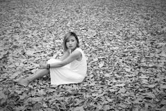 Young asian woman sadly sitting on dry leaf in the forest alone Stock Images