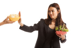 Young Asian woman with salad say no to potato chips. Stock Photo