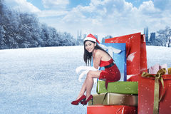 Young asian woman in santa costume sit on the gift box Royalty Free Stock Images