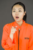 Young Asian woman scolding somebody in prisoners uniform Stock Photo