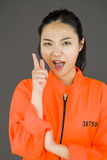 Young Asian woman scolding somebody in prisoners uniform Royalty Free Stock Photography