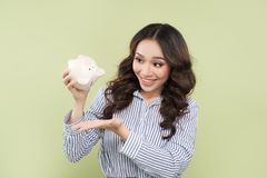 Young asian woman shaking out empty piggy bank on green backgrou. Nd Stock Image