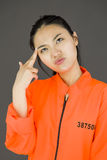 Young Asian woman shooting herself in head in prisoners uniform Royalty Free Stock Photo
