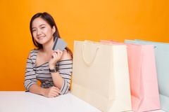 Young Asian woman with shopping bag and blank card. Royalty Free Stock Photography